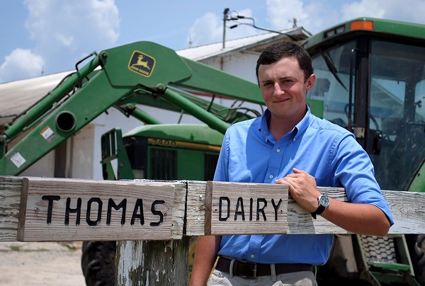 Photo of Chist Thomas standing in front of tractor