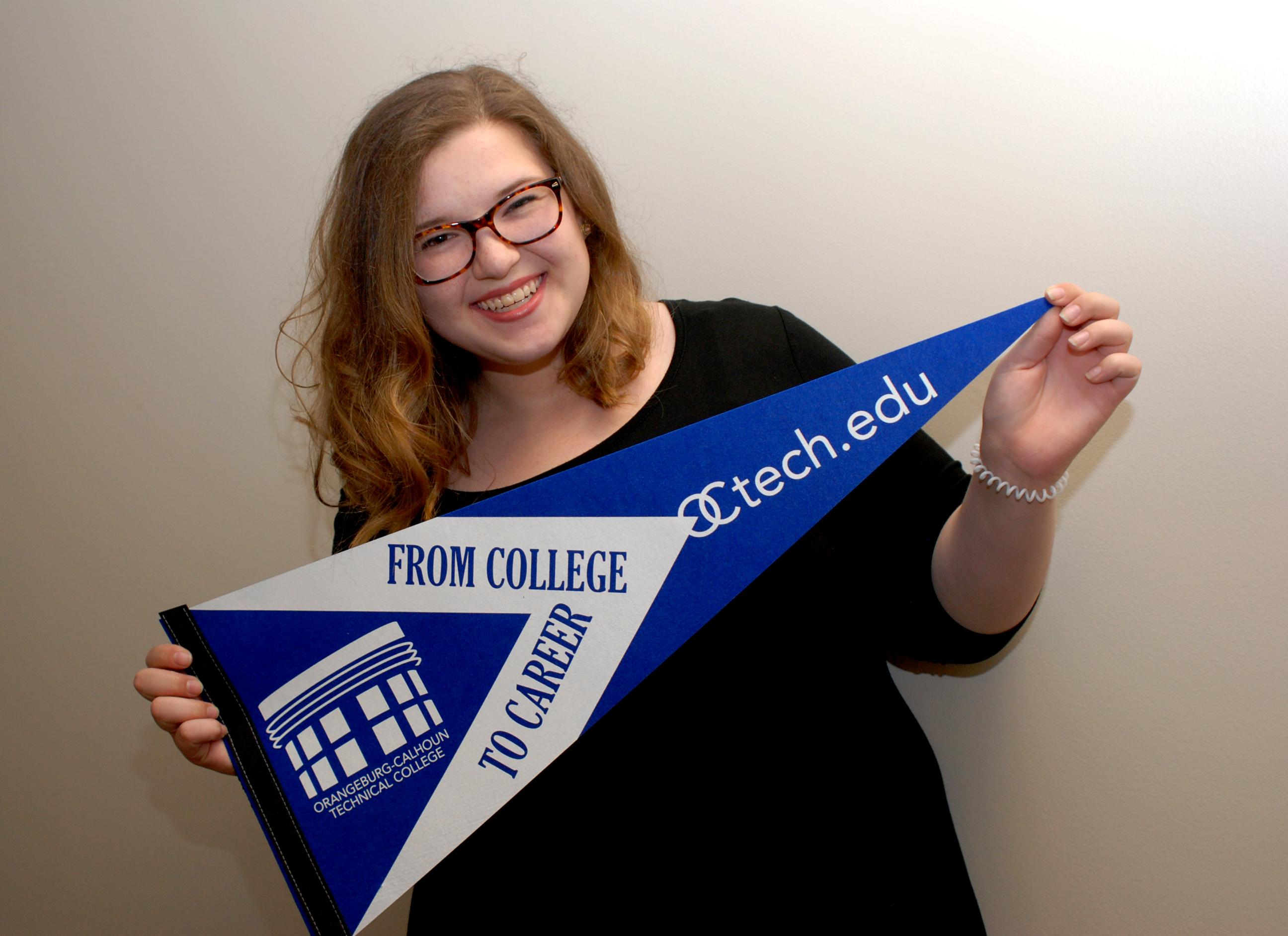 Student holding OCtech pennant