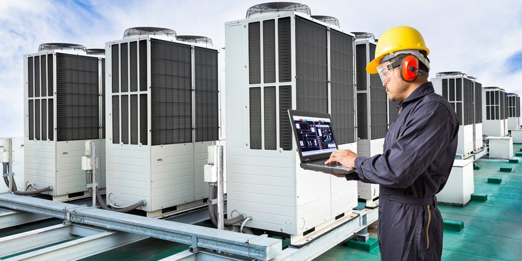 HVAC Tech with clipboard  with air conditioning units