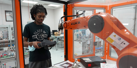 Student with robot in lab