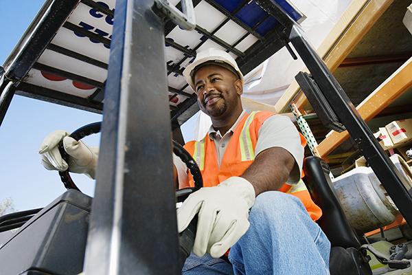 black man in hard hat and safety vest on a fork lift